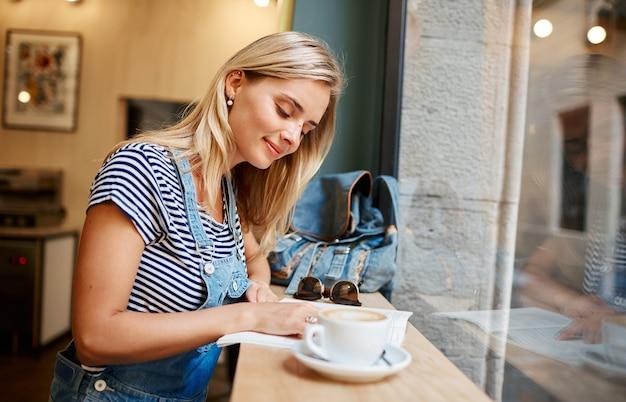 Junge blonde frau, die im café sitzt und liest