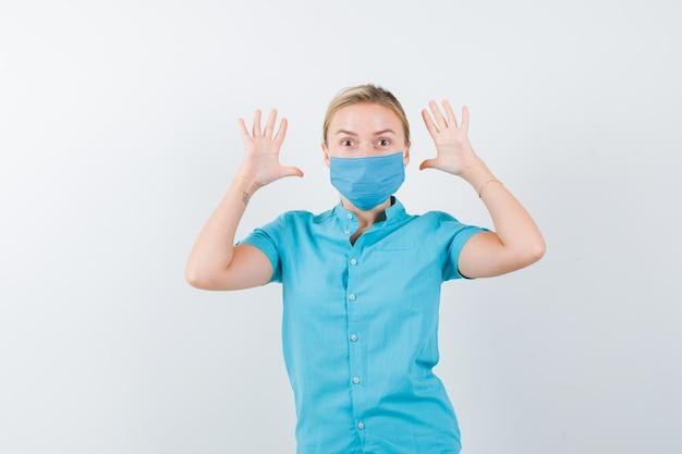Junge blonde frau, die kapitulationsgeste in freizeitkleidung, maske und angst zeigt