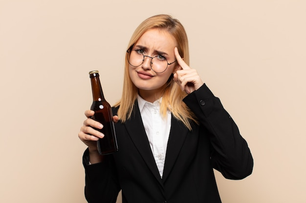 Junge blonde frau, die konzentriert aussieht und über eine idee nachdenkt und sich eine lösung für eine herausforderung oder ein problem vorstellt