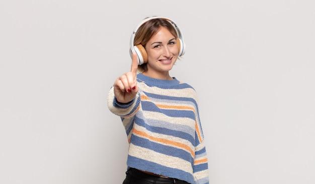 Junge blonde frau, die lächelt und freundlich aussieht, die nummer eins oder zuerst mit der hand nach vorne zeigt, herunterzählt