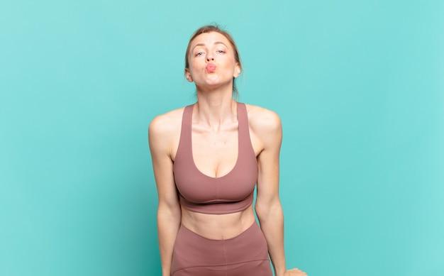 Junge blonde frau, die lippen mit einem netten, lustigen, glücklichen, reizenden ausdruck zusammendrückt und einen kuss schickt. sportkonzept