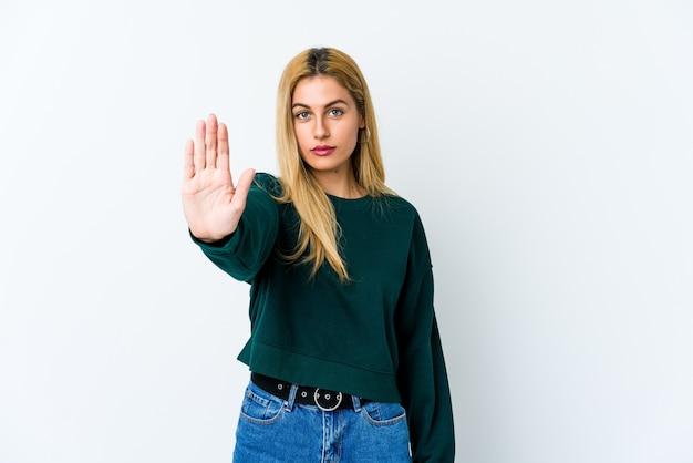Junge blonde frau, die mit ausgestreckter hand steht, die stoppschild zeigt, das sie verhindert.