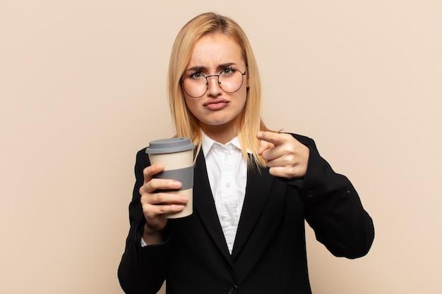 Junge blonde frau, die mit beiden fingern und wütendem ausdruck nach vorne in die kamera zeigt und ihnen sagt, sie sollen ihre pflicht tun