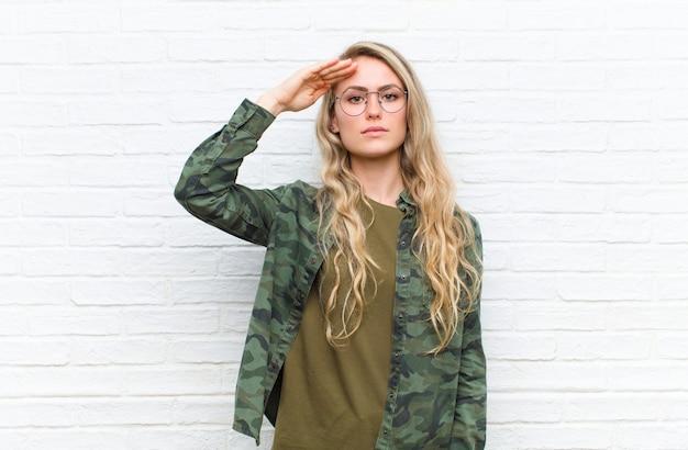 Junge blonde frau, die mit einem militärischen gruß in einem akt der ehre und des patriotismus grüßt und respekt gegen mauer zeigt