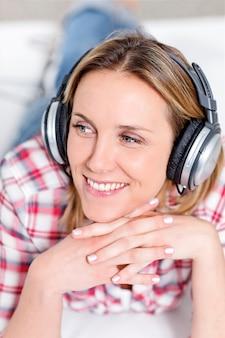 Junge blonde frau, die musik mit kopfhörern hört