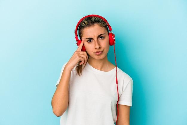 Junge blonde frau, die musik über kopfhörer hört, die auf blauem hintergrund isoliert ist und mit dem finger auf den tempel zeigt, denkt, konzentriert sich auf eine aufgabe.