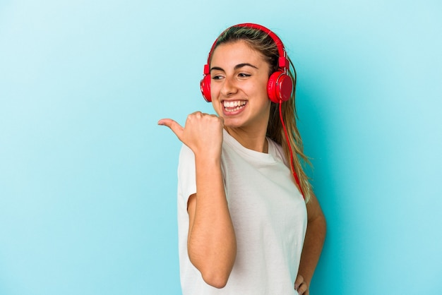 Junge blonde frau, die musik über kopfhörer hört, die auf blauem hintergrund isoliert ist, zeigt mit dem daumen weg, lacht und sorglos.