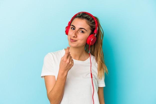 Junge blonde frau, die musik über kopfhörer hört, einzeln auf blauem hintergrund, die mit dem finger auf sie zeigt, als ob sie einladen würde, näher zu kommen.