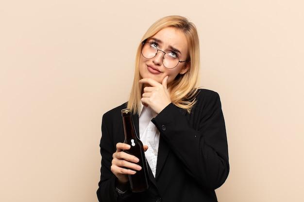Junge blonde frau, die nachdenklich fühlt, sich wundert oder ideen vorstellt, tagträumen und aufschaut, um raum zu kopieren