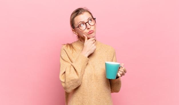 Junge blonde frau, die nachdenkt, sich zweifelnd und verwirrt fühlt, mit verschiedenen optionen und sich fragt, welche entscheidung sie treffen soll. kaffeekonzept