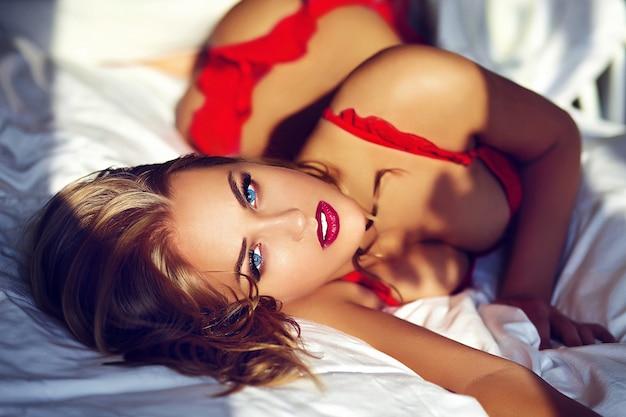 Junge blonde frau, die rote wäsche auf bett am morgen trägt