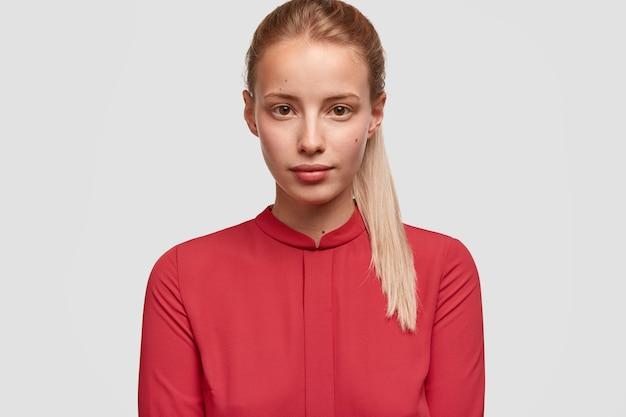 Junge blonde frau, die rotes hemd trägt