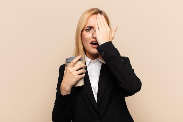 Junge blonde frau, die schläfrig, gelangweilt und gähnend aussieht, mit kopfschmerzen und einer hand, die das halbe gesicht bedeckt