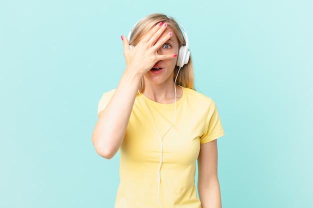 Junge blonde frau, die schockiert, verängstigt oder verängstigt aussieht, das gesicht mit der hand bedeckt und musik hört.