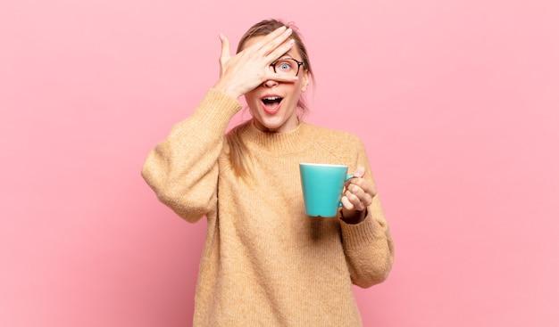 Junge blonde frau, die schockiert, verängstigt oder verängstigt aussieht, das gesicht mit der hand bedeckt und zwischen den fingern späht. kaffeekonzept