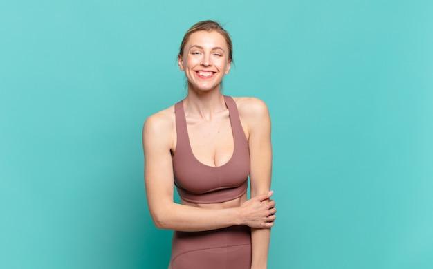 Junge blonde frau, die schüchtern und fröhlich lacht, mit einer freundlichen und positiven, aber unsicheren einstellung. sportkonzept