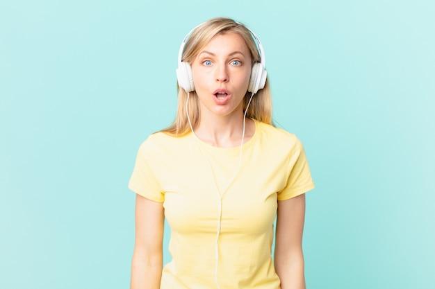 Junge blonde frau, die sehr schockiert oder überrascht aussieht und musik hört.