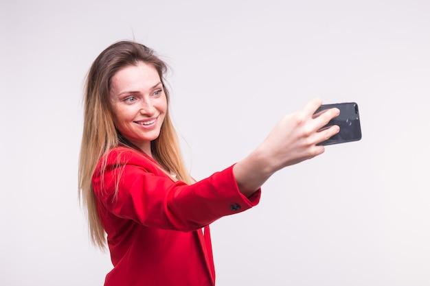 Junge blonde frau, die selfie im studio macht