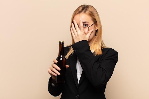 Junge blonde frau, die sich ängstlich oder verlegen fühlt, mit halb mit händen bedeckten augen späht oder spioniert