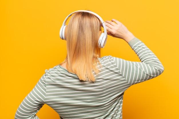 Junge blonde frau, die sich ahnungslos und verwirrt fühlt und eine lösung denkt, mit der hand auf der hüfte und anderen auf dem kopf, rückansicht