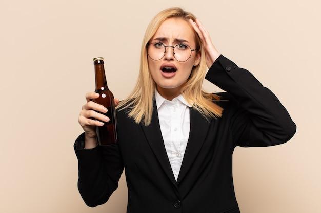 Junge blonde frau, die sich entsetzt und geschockt fühlt, hände zum kopf hebt und bei einem fehler in panik gerät