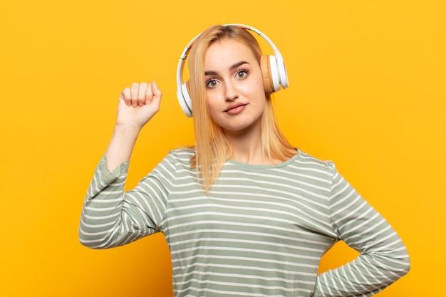 Junge blonde frau, die sich ernst, stark und rebellisch fühlt, die faust erhebt, protestiert oder für die revolution kämpft