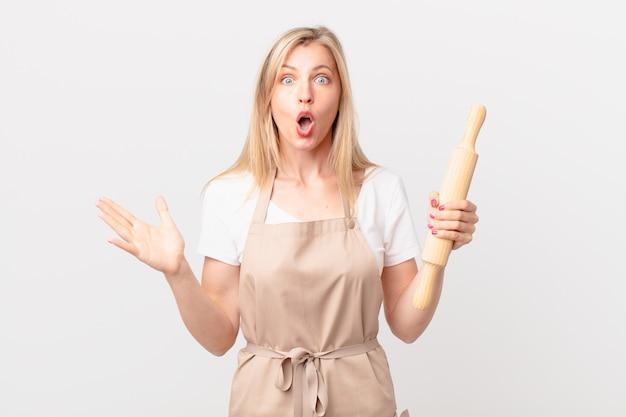 Junge blonde frau, die sich extrem schockiert und überrascht fühlt. bäckerkonzept