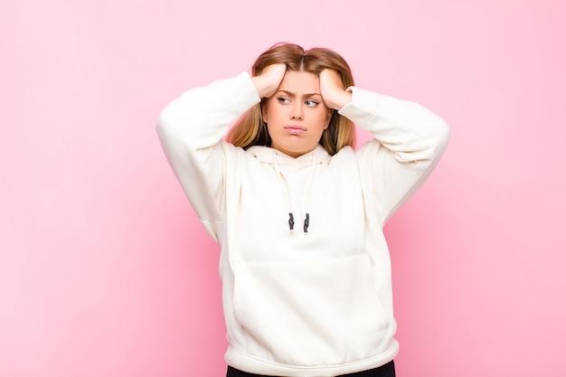 Junge blonde frau, die sich frustriert und genervt fühlt, krank und müde vom versagen, satt von langweiligen, langweiligen aufgaben gegen flache wand