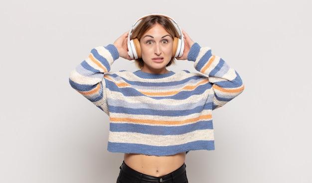Junge blonde frau, die sich gestresst, besorgt, ängstlich oder ängstlich fühlt, mit händen auf dem kopf, die bei einem fehler in panik geraten