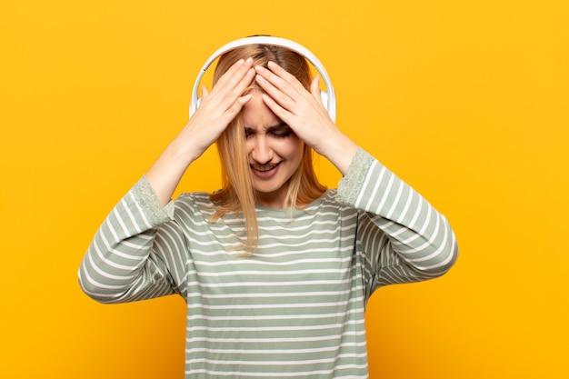 Junge blonde frau, die sich gestresst und frustriert fühlt, hände zum kopf hebt, sich müde, unglücklich und mit migräne fühlt