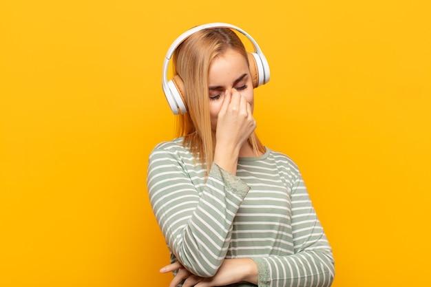 Junge blonde frau, die sich gestresst, unglücklich und frustriert fühlt, die stirn berührt und unter migräne mit starken kopfschmerzen leidet