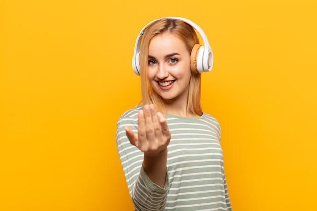 Junge blonde frau, die sich glücklich, erfolgreich und selbstbewusst fühlt, sich einer herausforderung stellt und sagt, bringen sie es auf! oder dich begrüßen