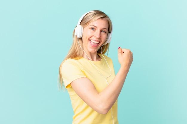 Junge blonde frau, die sich glücklich fühlt und einer herausforderung gegenübersteht oder musik feiert und hört.