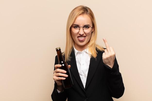 Junge blonde frau, die sich provokativ, aggressiv und obszön fühlt und den mittelfinger mit einer rebellischen haltung umdreht