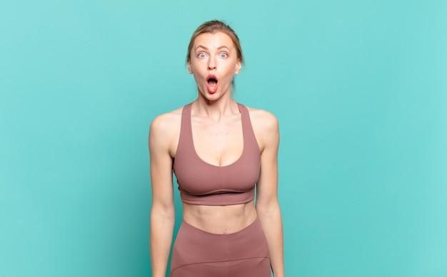 Junge blonde frau, die sich verängstigt und schockiert fühlt, mit vor überraschung weit geöffnetem mund. sportkonzept