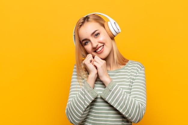Junge blonde frau, die sich verliebt fühlt und niedlich, entzückend und glücklich schaut, romantisch mit den händen neben gesicht lächelnd