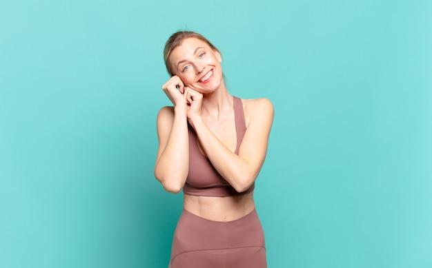 Junge blonde frau, die sich verliebt fühlt und süß, bezaubernd und glücklich aussieht und romantisch mit den händen neben dem gesicht lächelt. sportkonzept