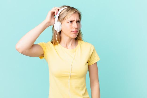 Junge blonde frau, die sich verwirrt und verwirrt fühlt, den kopf kratzt und musik hört.