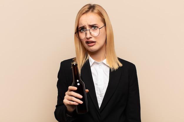 Junge blonde frau, die sich verwirrt und verwirrt fühlt, mit einem dummen, fassungslosen ausdruck, der etwas unerwartetes betrachtet