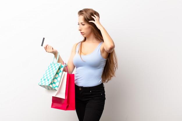Junge blonde frau, die sich verwirrt und verwirrt fühlt, sich am kopf kratzt und zur seite schaut und einkaufstaschen hält
