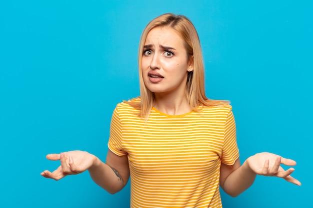 Junge blonde frau, die sich verwirrt und verwirrt fühlt, sich über die richtige antwort oder entscheidung nicht sicher ist und versucht, eine wahl zu treffen