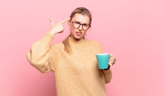 Junge blonde frau, die sich verwirrt und verwirrt fühlt und zeigt, dass sie verrückt, verrückt oder verrückt sind. kaffeekonzept