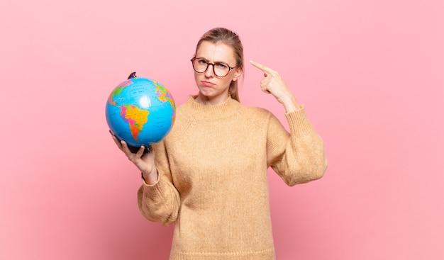 Junge blonde frau, die sich verwirrt und verwirrt fühlt und zeigt, dass sie verrückt, verrückt oder verrückt sind. weltkonzept