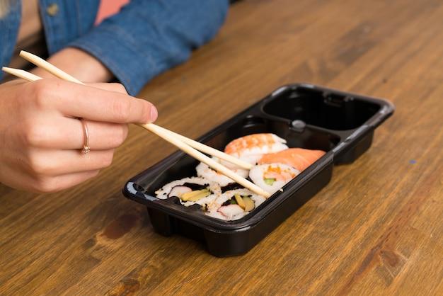Junge blonde frau, die sushi isst