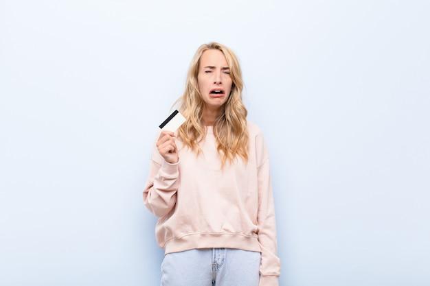 Junge blonde frau, die traurig und weinerlich mit einem unglücklichen blick fühlt und mit einer negativen und frustrierten haltung weint, die eine kreditkarte hält