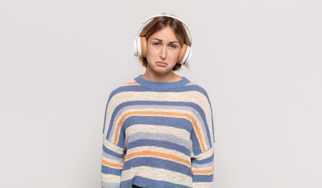 Junge blonde frau, die traurig und weinerlich mit einem unglücklichen blick fühlt und mit einer negativen und frustrierten haltung weint