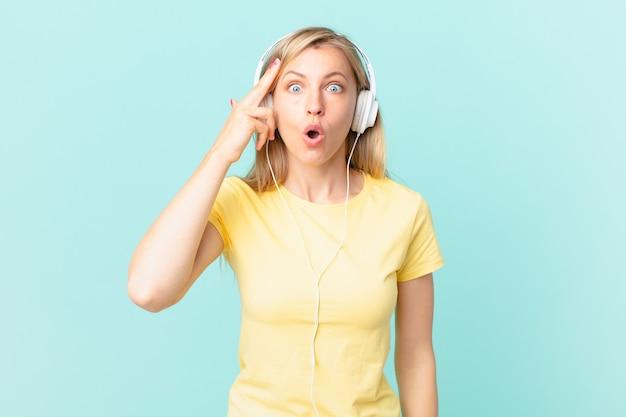 Junge blonde frau, die überrascht aussieht, einen neuen gedanken, eine neue idee oder ein neues konzept realisiert und musik hört.