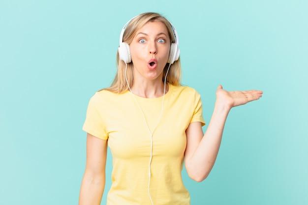 Junge blonde frau, die überrascht und schockiert aussieht, mit heruntergefallenem kiefer, die einen gegenstand hält und musik hört.