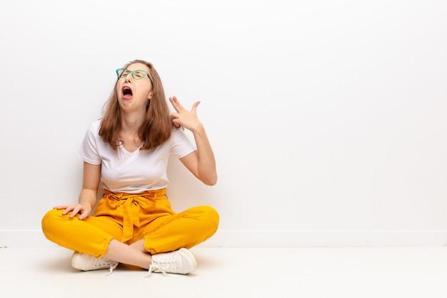 Junge blonde frau, die unglücklich und gestresst aussieht, selbstmordgeste, die waffenzeichen mit der hand macht, zeigt auf kopf, der auf dem boden sitzt