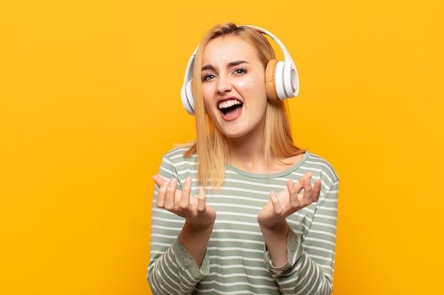 Junge blonde frau, die verzweifelt und frustriert, gestresst, unglücklich und genervt aussieht, schreit und schreit